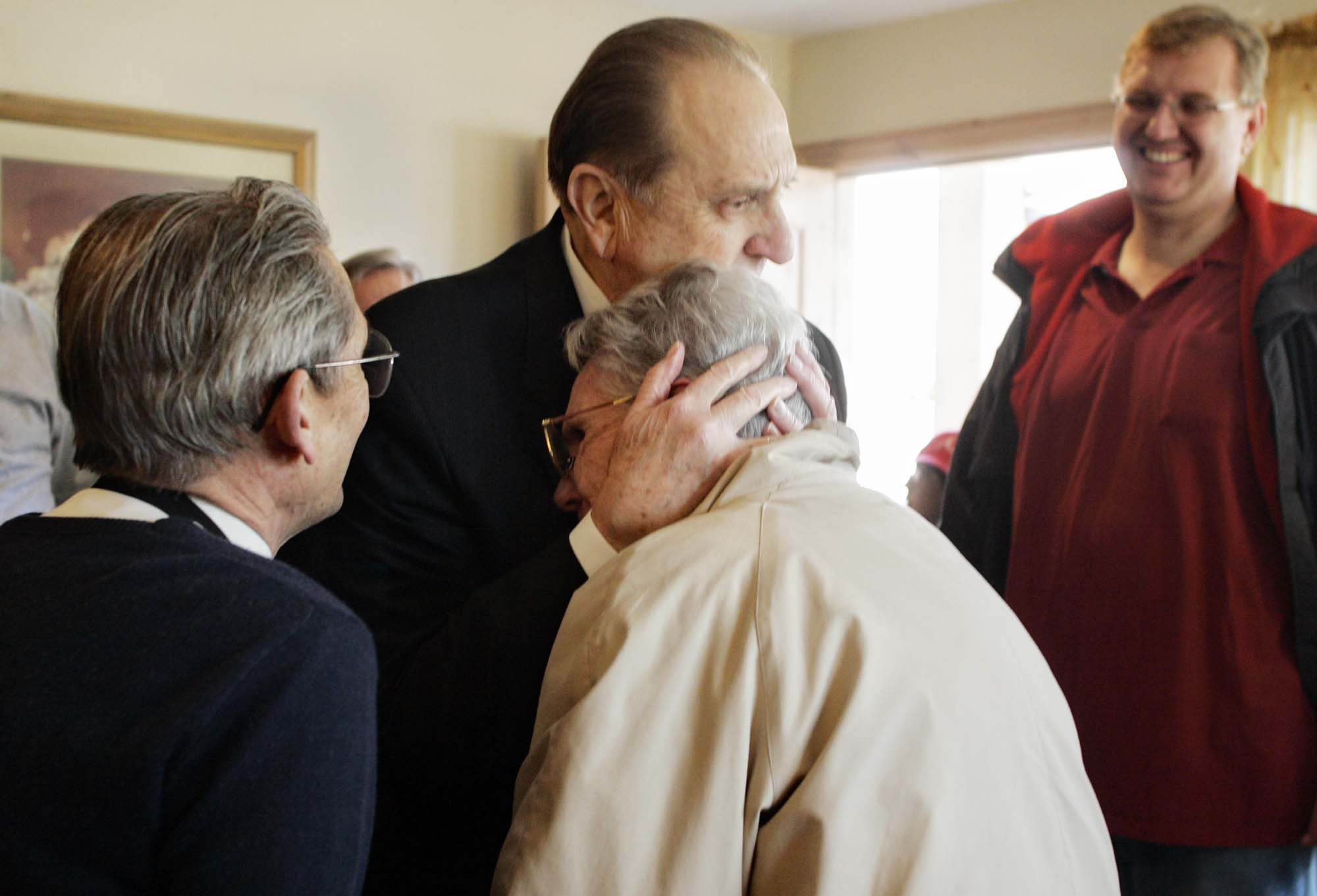(Tribune file photo) President Thomas S. Monson embraces Adele Putnam after her familyÕs home was renovated as part of the Gingerbread House Project in 2005.
