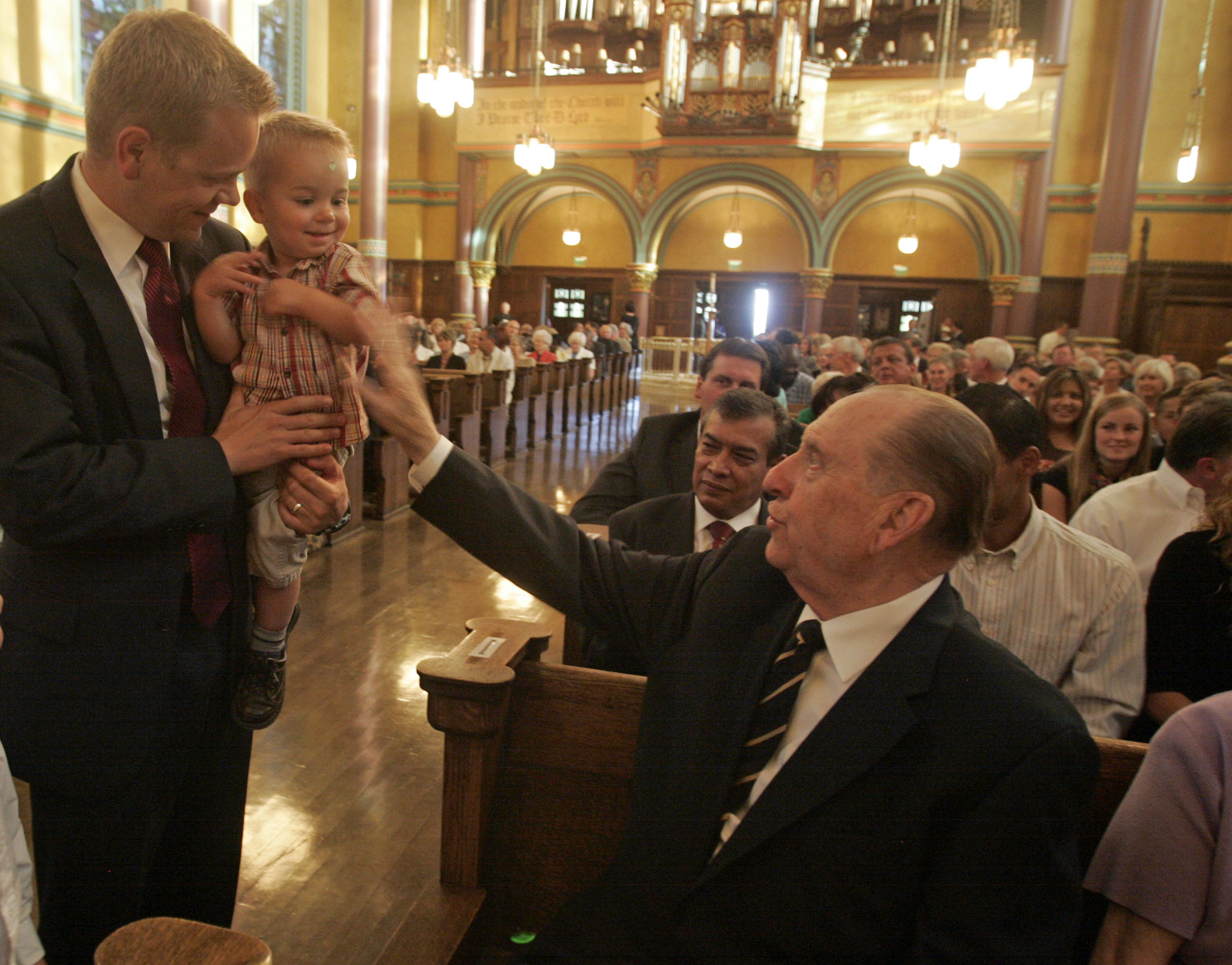 (Tribune file photo) President Thomas S. Monson visits with Scott Daw of Herriman and Daw's 1-year-old son, Brennan Daw during an event at the Cathedral of the Madeleine in August 2012.