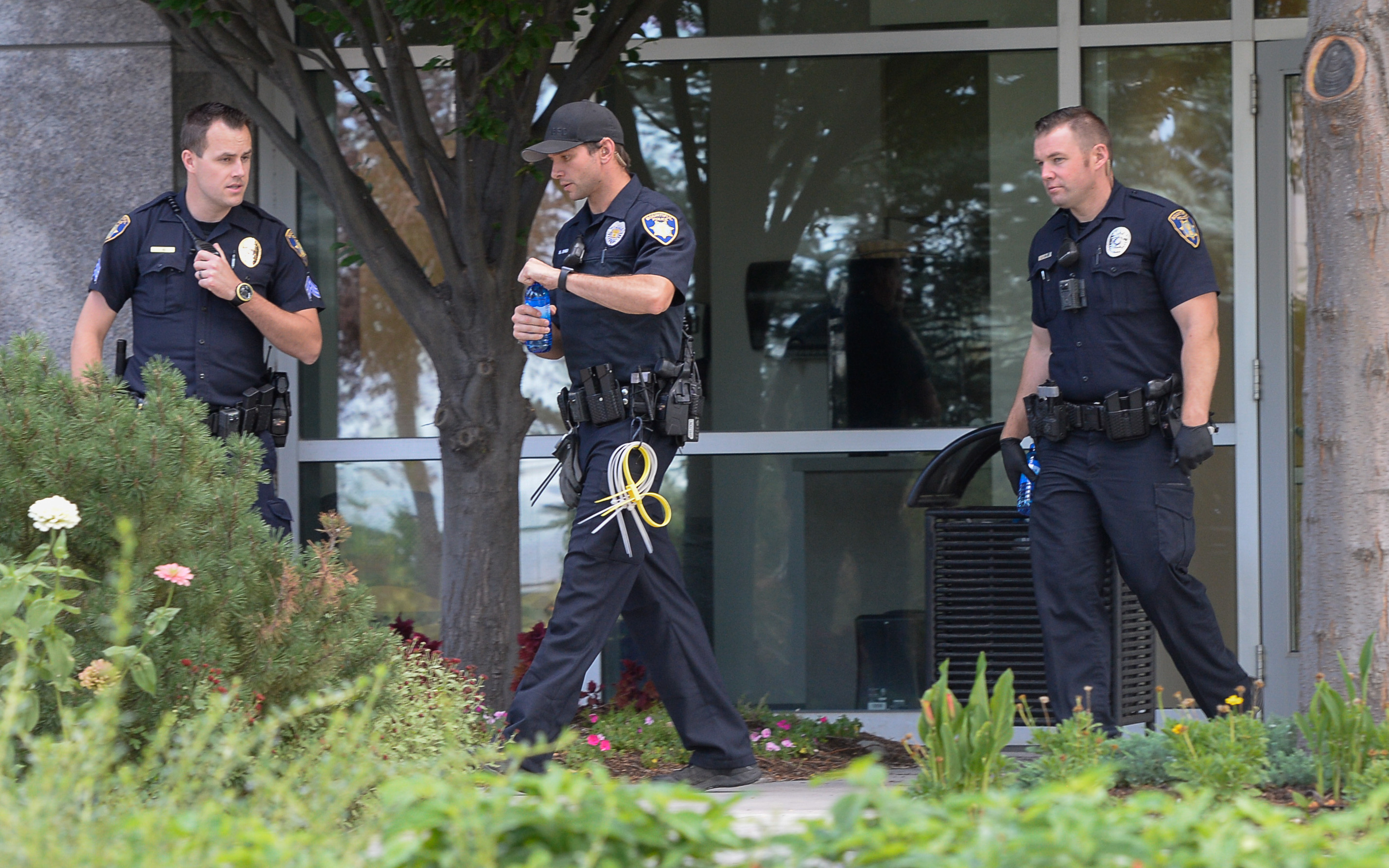 (Francisco Kjolseth  |  The Salt Lake Tribune)  Law enforcement leaves the building where activists staged a protest against a private prison company with contracts to hold undocumented immigrants on Thursday, July 12, 2018, at the headquarters of Management and Training Corporation in Centerville.