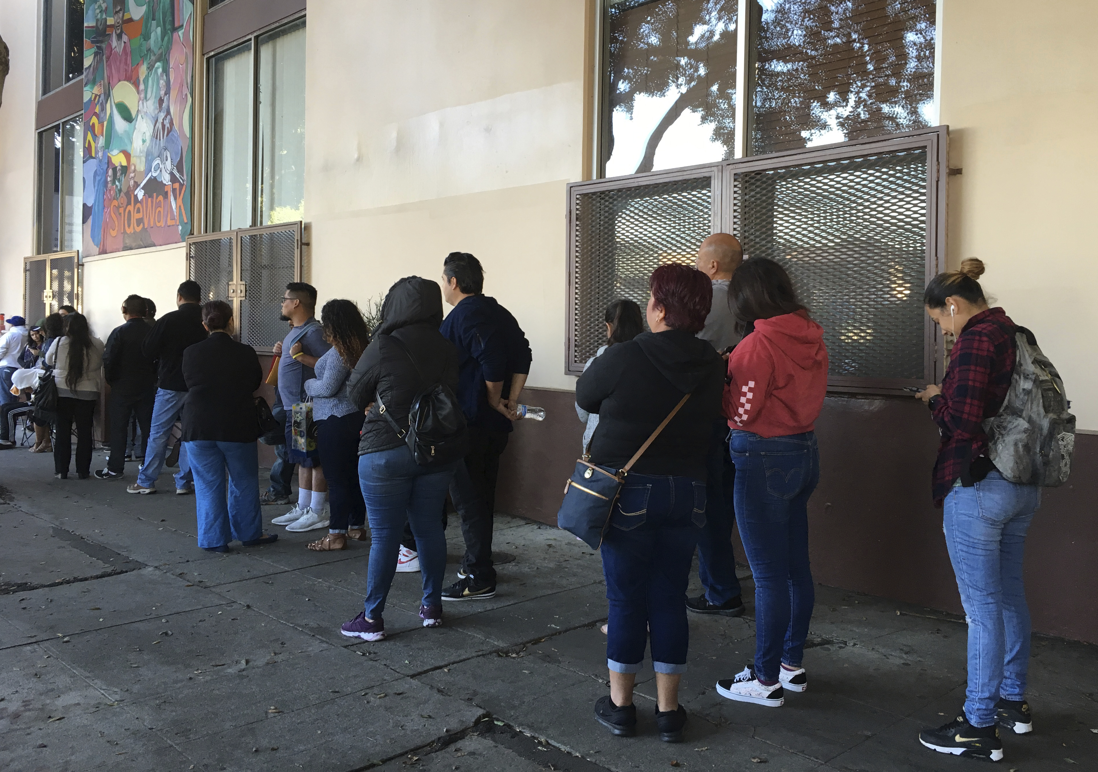 Immigrants line up to renew work permits as program ends ...