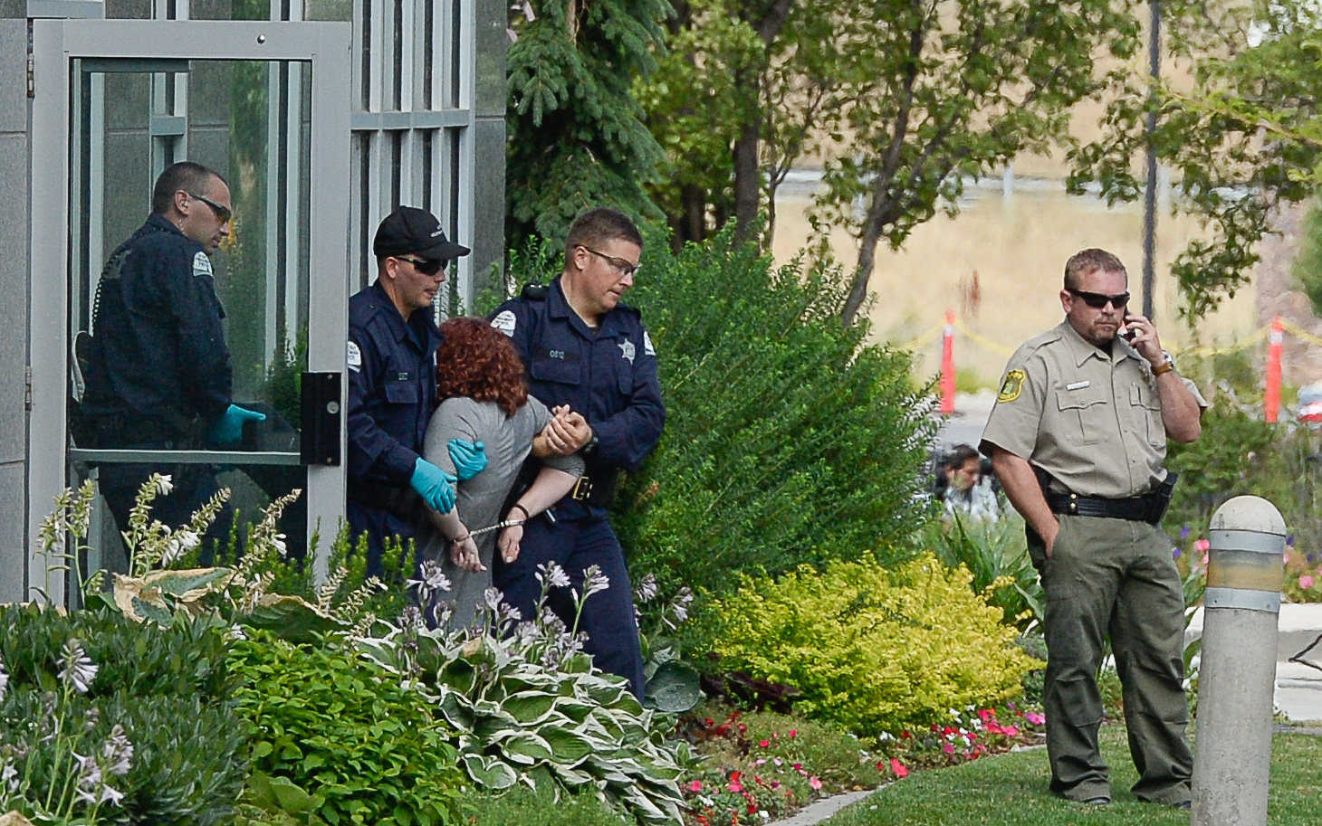 (Francisco Kjolseth  |  The Salt Lake Tribune)  Activists are escorted out of a building where they staged a protest against a private prison company with contracts to hold undocumented immigrants on Thursday, July 12, 2018, at the headquarters of Management and Training Corporation in Centerville.