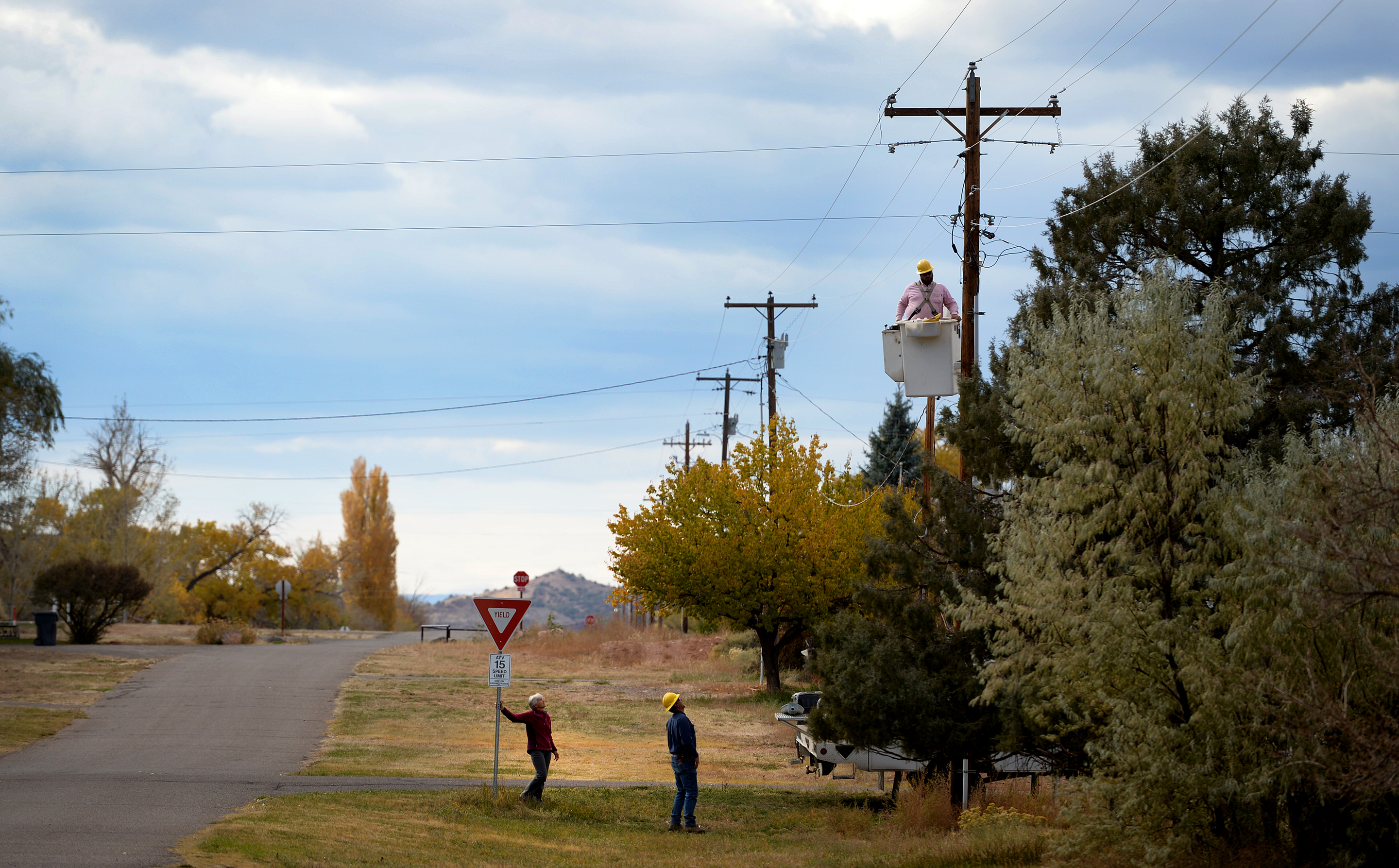 (Leah Hogsten  |  The Salt Lake Tribune) Torrey resident Mary Bedingfieldsmith, left, watches as workers from Garkane Energy Cooperative replace the remaining four sodium vapor lights on 100 North with new lights, using spectra at 3000 Kelvin or less, that direct light away from the sky, Oct. 19, 2017.  Torrey, the gateway town to Capitol Reef National Park, has applied to become the state's first Dark Sky Community.