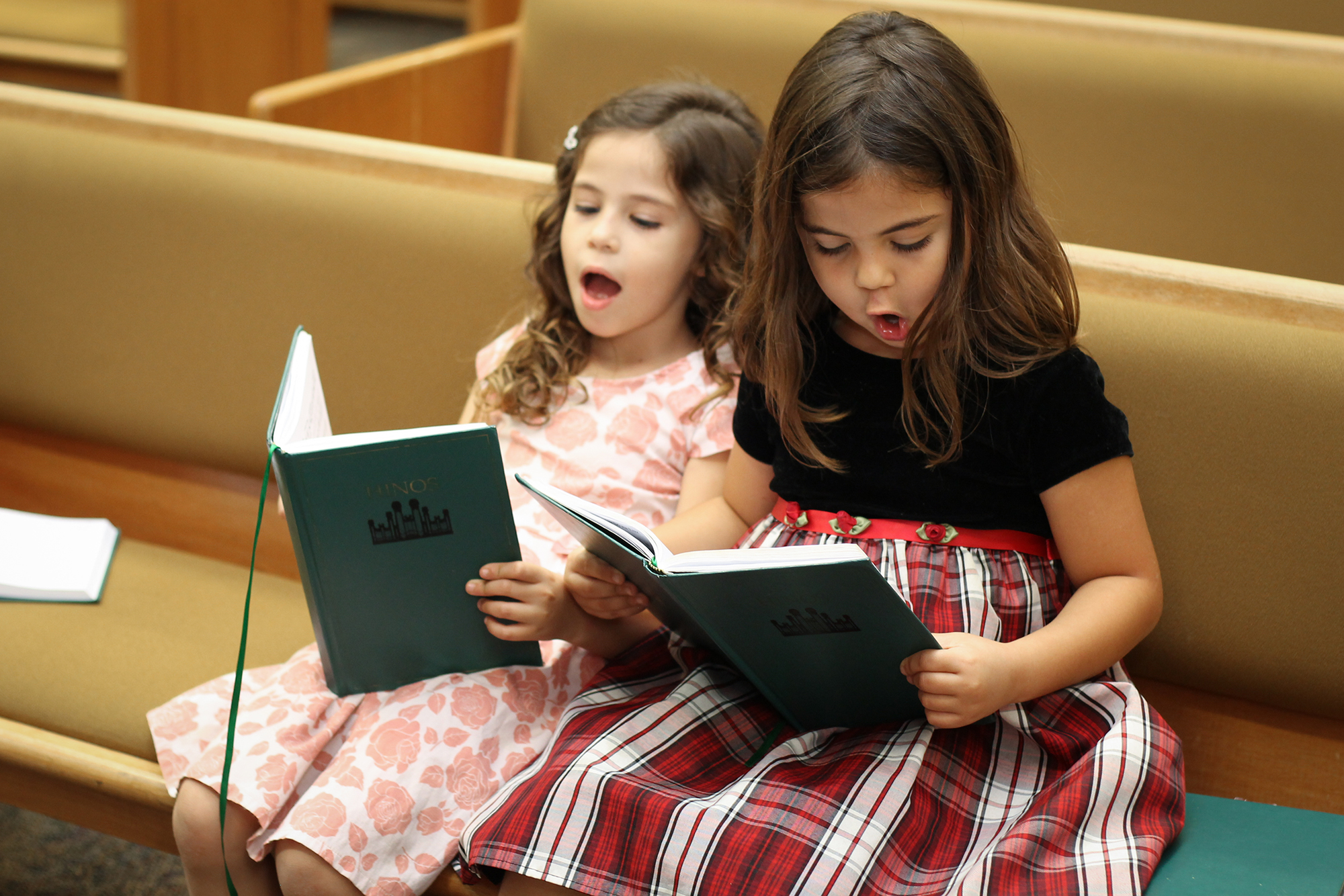 (Courtesy LDS Church) Two girls sing from a Latter-day Saint hymnbook.