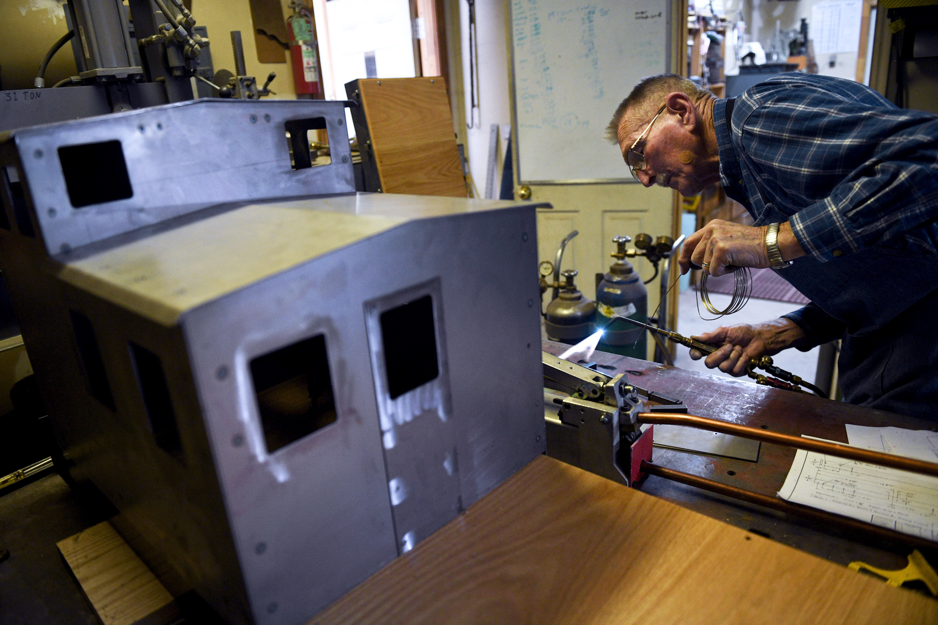 ADVANCE FOR USE WITH WEEKEND EDITIONS JULY 7-8, 2018 AND THEREAFTER In this Tuesday, June 19, 2018 photo, Jim Smeltzer welds a miniature ladder which will eventually attach to the back of the caboose in his workshop at his home in Highland, Utah. Since 2004, the Smeltzers' land surrounding their home has been a model railyard.  (Isaac Hale/The Daily Herald via AP)