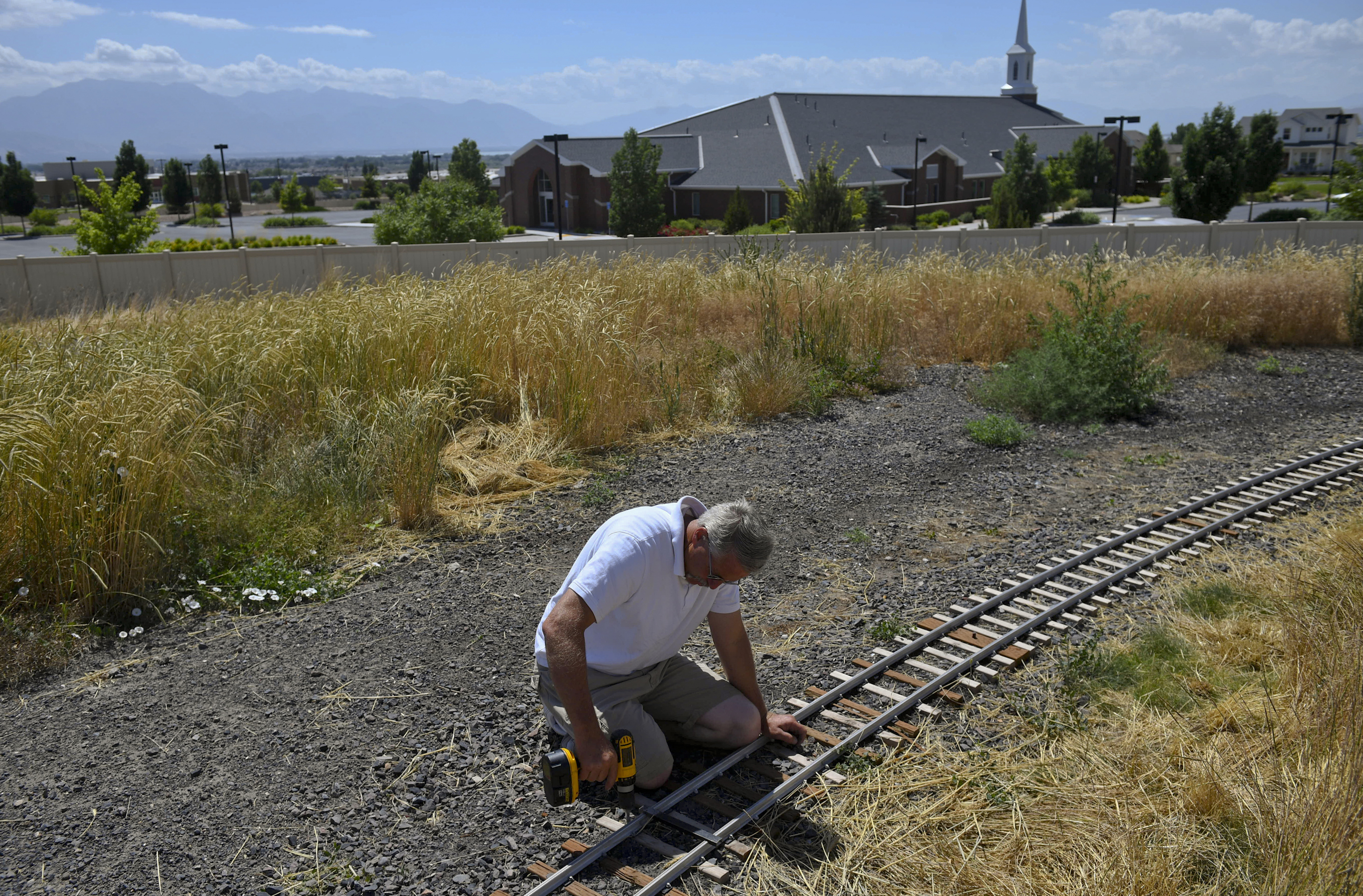 """ADVANCE FOR USE WITH WEEKEND EDITIONS JULY 7-8, 2018 AND THEREAFTER In this Saturday, June 16, 2018 photo, Mike Hansen, co-founder of the Utah Live Steamers Railroad Club, corrects a heat kink in a section of track during public train rides held by Utah Live Steamers at Shay Park in Saratoga Springs, Utah. Shay Park's name has to do with the history of railroads in the area. """"A lot of these communities were built because of the railroad,"""" explained Hansen. """"At one point, you could get on a train here and go anywhere in the country.""""  (Isaac Hale/The Daily Herald via AP)"""