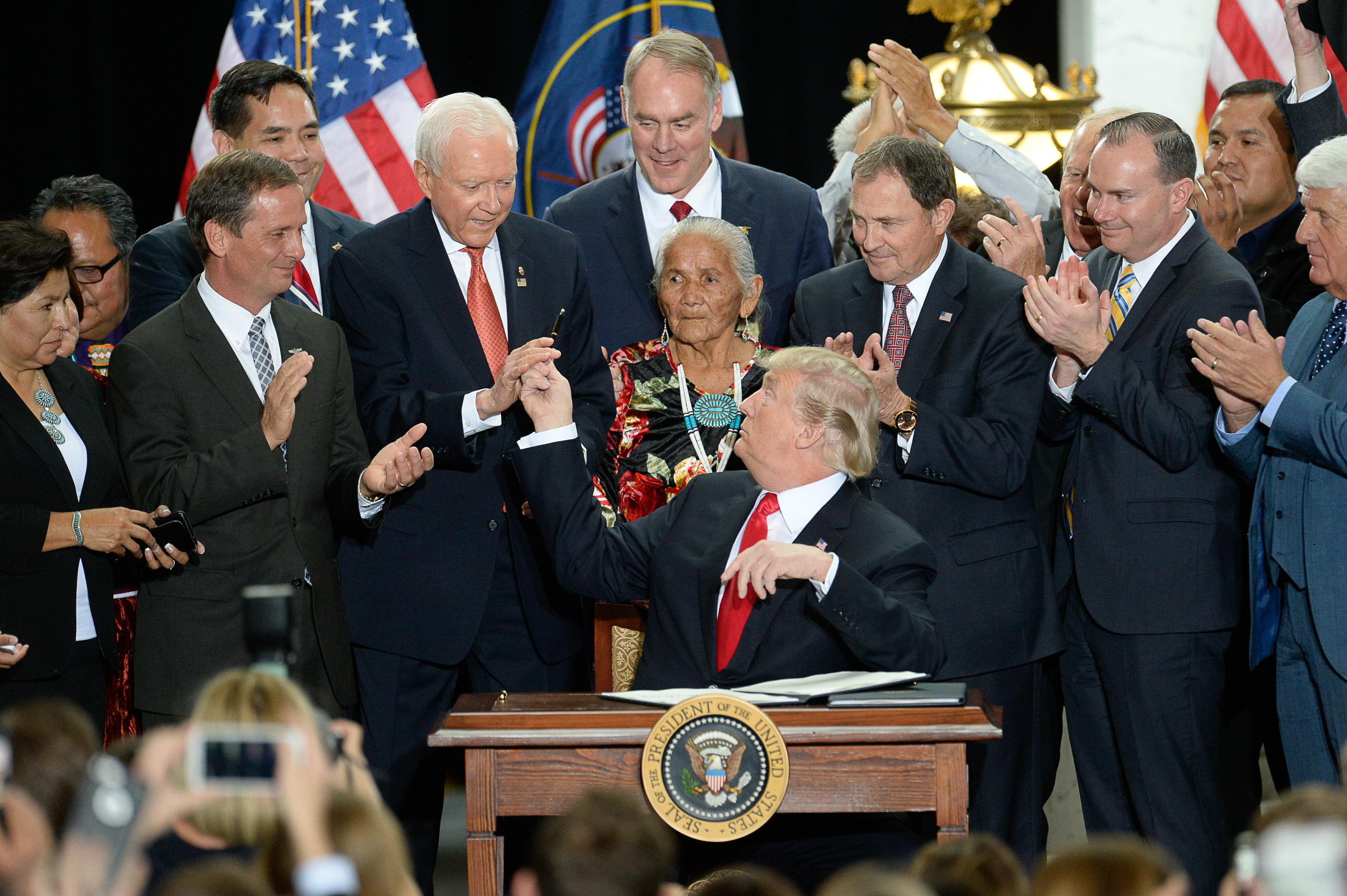(Francisco Kjolseth  |  Tribune file photo)  U.S. President Donald Trump, surrounded by Utah representatives looks at Sen. Orrin Hatch to give him the pen used to signs a presidential proclamation to shrink Bears Ears and Grand Staircase-Escalante national monuments at the Utah Capitol on Monday, Dec. 4, 2017.