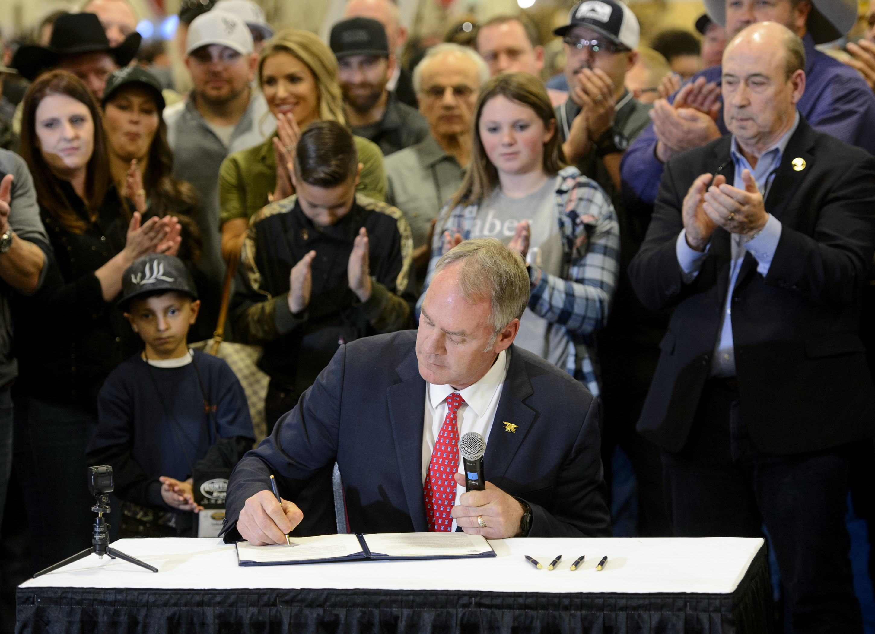 (Steve Griffin  |  The Salt Lake Tribune)  U.S. Secretary of the Interior Ryan Zinke, in an appearance at the Western Hunting and Conservation Expo at the Salt Palace Convention Center in Salt Lake City, signs Secretarial Order 3362, aimed at improving habitat quality and Western winter range and migration corridors for big game.