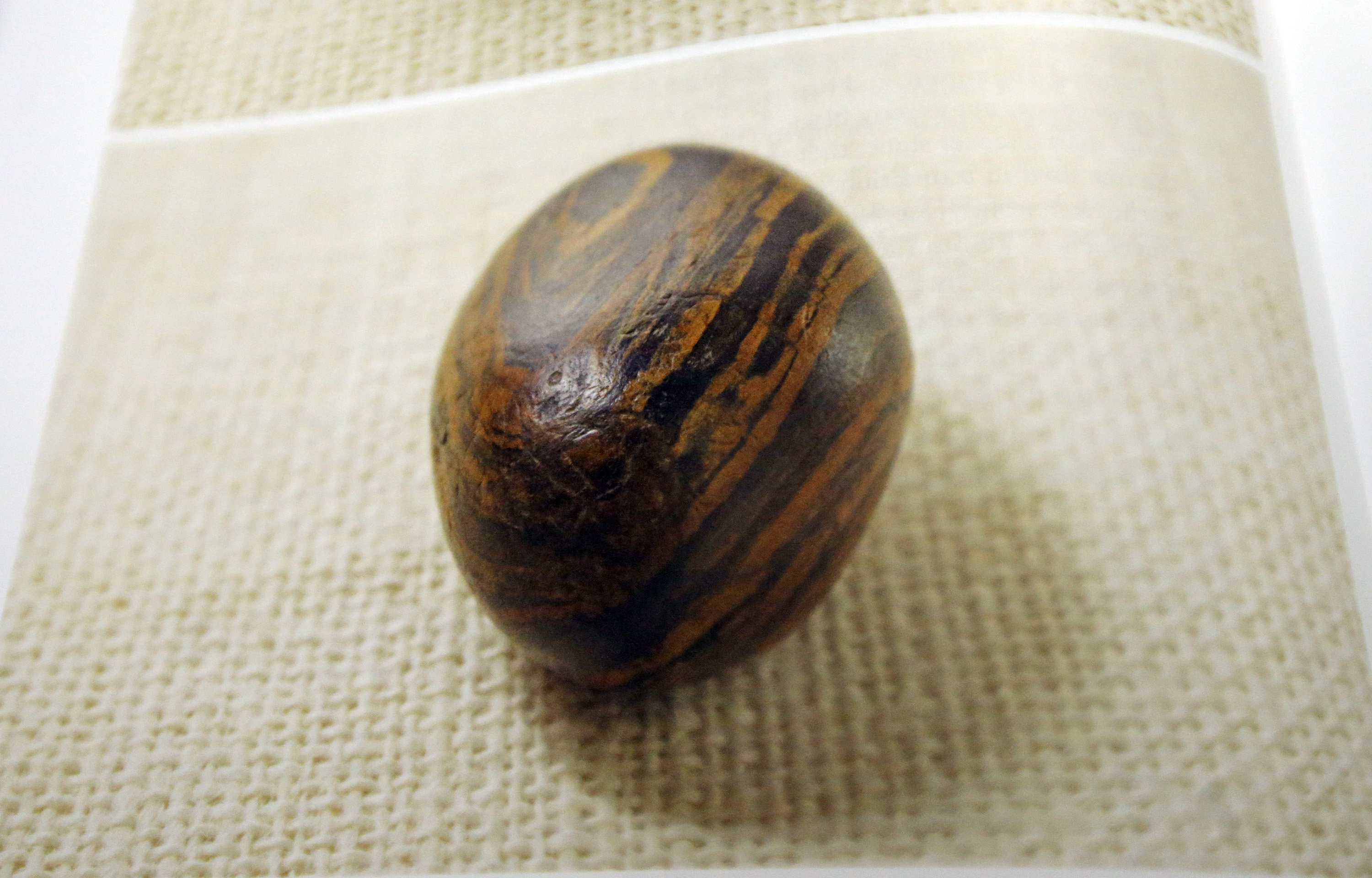 """(AP Photo/Rick Bowmer) A picture of a smooth, brown, egg-size rock is shown in the printer's manuscript of the Book of Mormon following a news conference Tuesday, Aug. 4, 2015, at the Church of Jesus Christ of Latter-day Saints Church History Library, in Salt Lake City. The church published photos of a small """"seer stone"""" it believes founder Joseph Smith used to help translate its foundational scripture."""