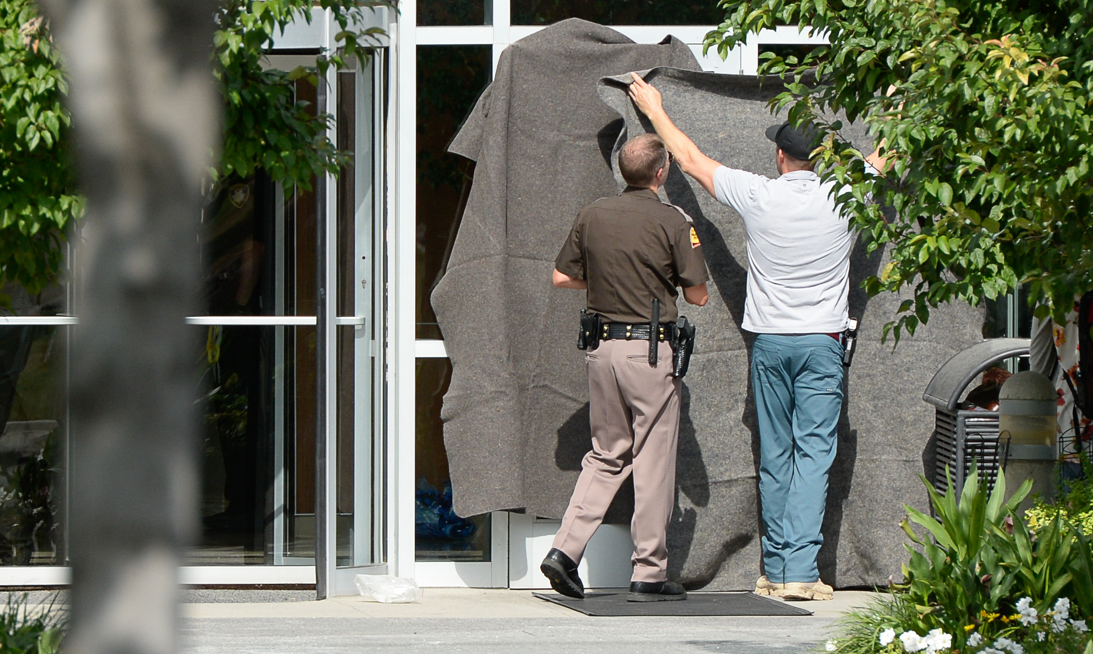 (Francisco Kjolseth  |  The Salt Lake Tribune)  Law enforcement covers up the windows where ctivists staged a protest against a private prison company with contracts to hold undocumented immigrants on Thursday, July 12, 2018, after locking themselves in the lobby at the headquarters of Management and Training Corporation in Centerville.