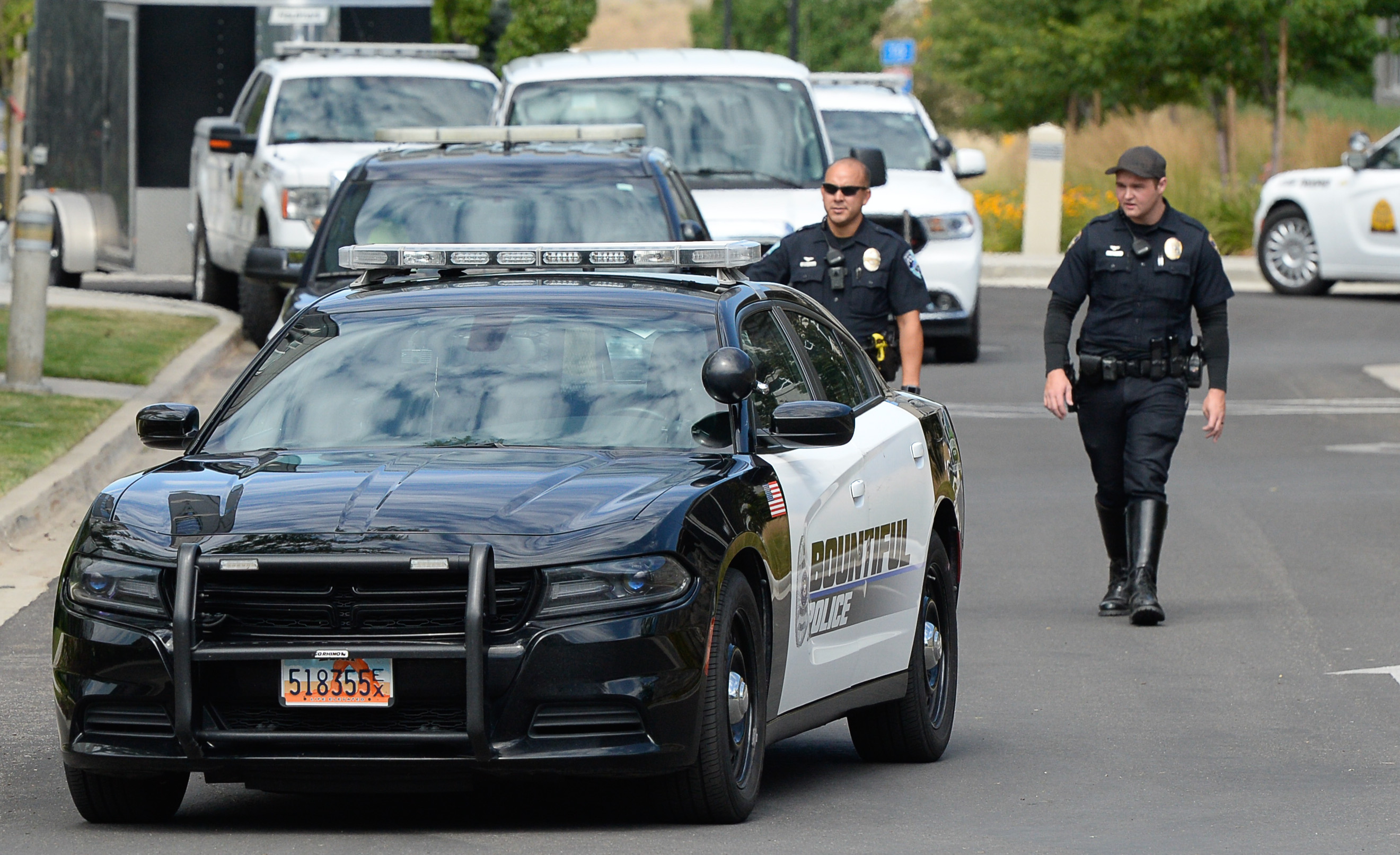 (Francisco Kjolseth  |  The Salt Lake Tribune)  Police gather at the scene where activists staged a protest against a private prison company with contracts to hold undocumented immigrants on Thursday, July 12, 2018, at the headquarters of Management and Training Corporation in Centerville.