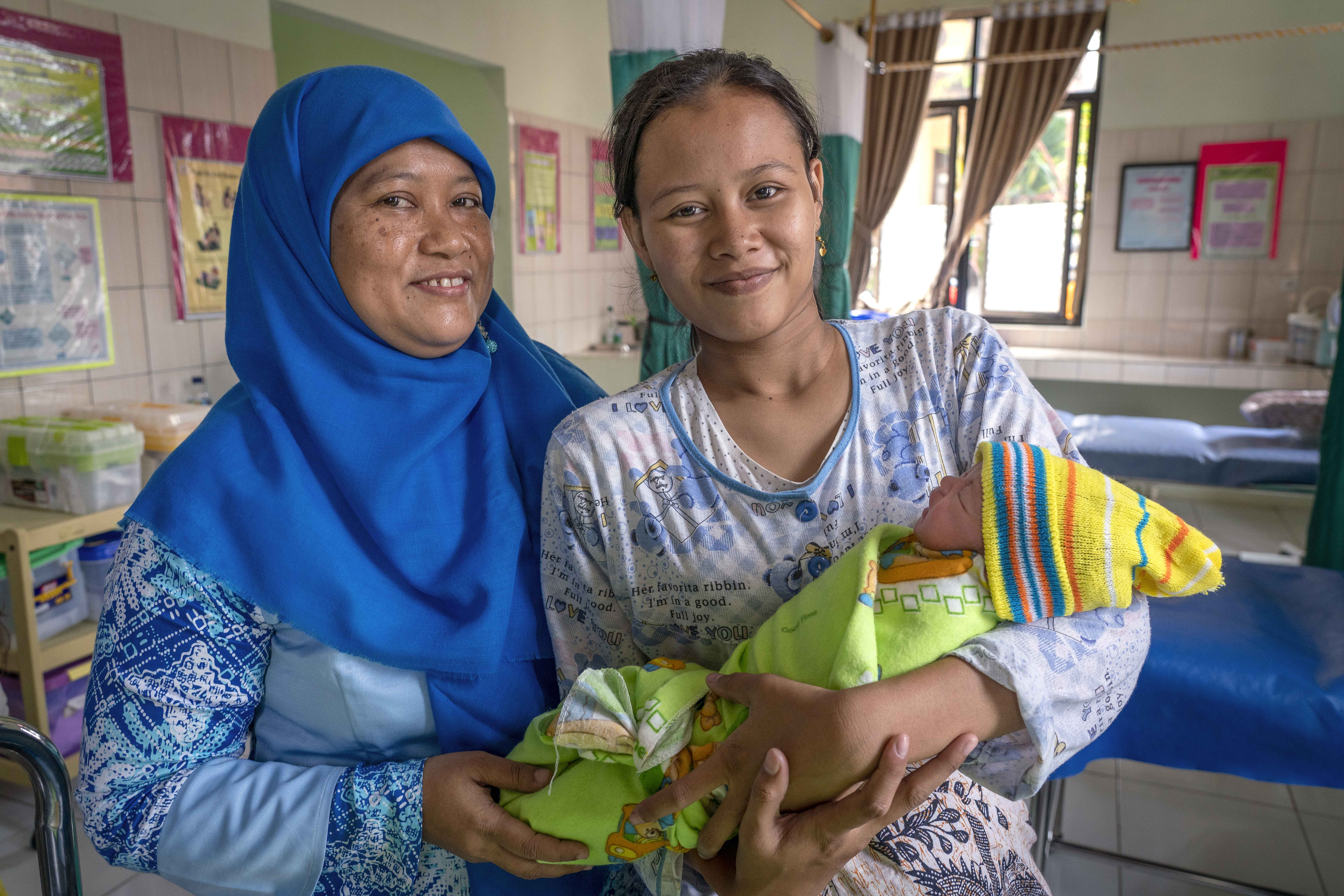 (Photo courtesy of The Church of Jesus Christ of Latter-day Saints) A nurse in Banyumas, Indonesia, stands next to a new mother. In 2018, nurses in this birthing center completed a Helping Babies Breathe course run by LDS Charities facilitators.