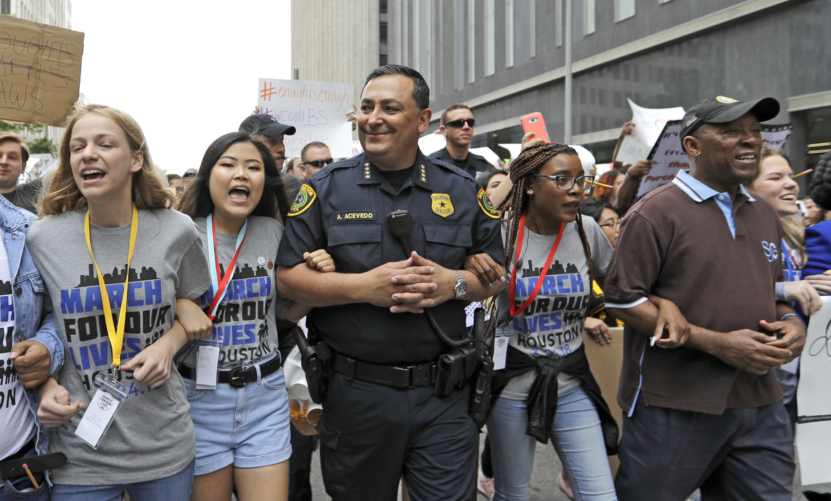 """Houston Police Chief Art Acevedo, center, and Houston Mayor Sylvester Turner, far right, join demonstrators during a """"March for Our Lives"""" protest for gun legislation and school safety Saturday, March 24, 2018, in Houston. Turner has told several thousand people demonstrating for stricter gun control that adults have a responsibility to stand up and protect all children. (AP Photo/David J. Phillip)"""